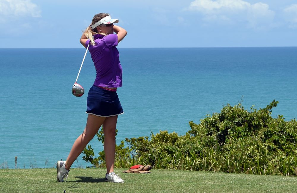 Woman golfing with ocean behind her
