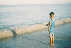 little boy fishing on the beach