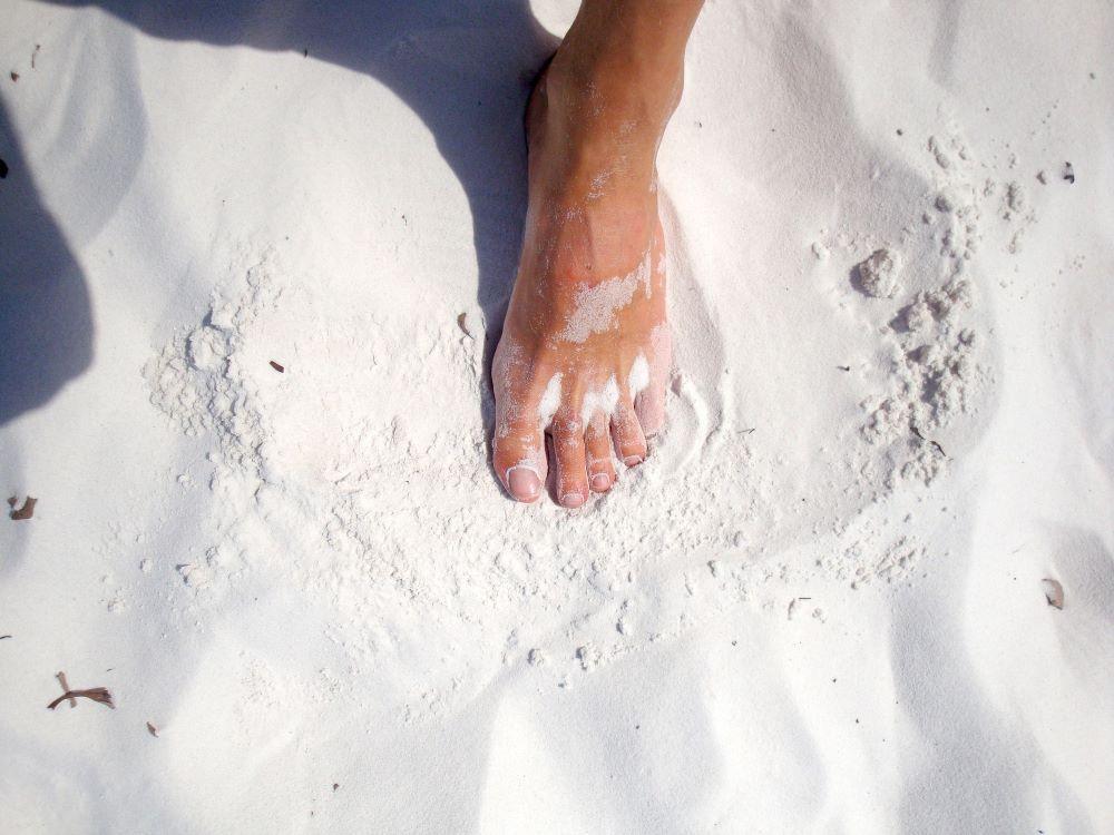 foot walking in white sand