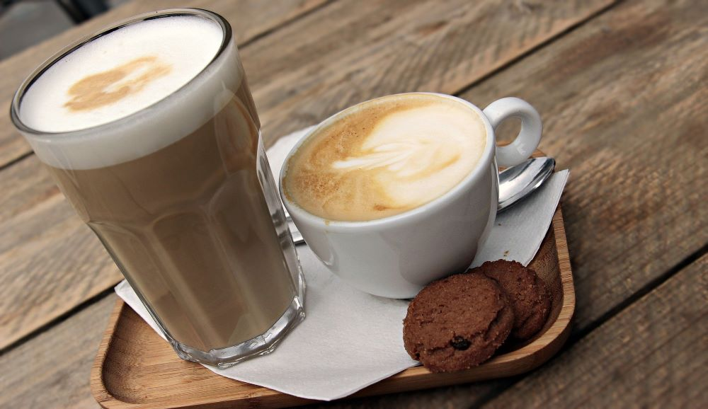 coffee drinks and cookies on a counter