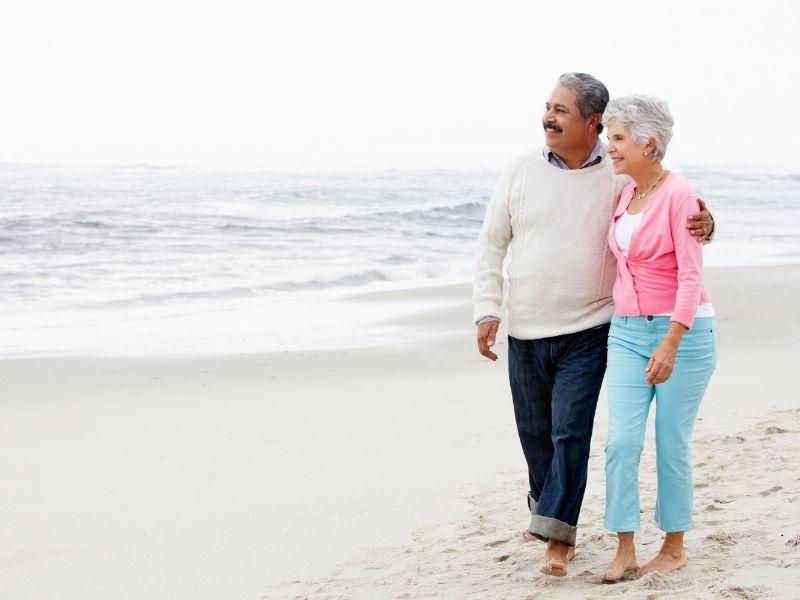 couples walking the beach shoreline