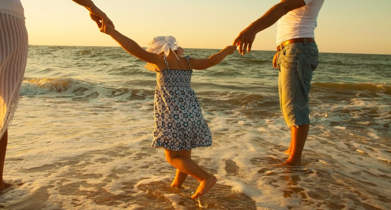 child playing in the water holding onto parents hands