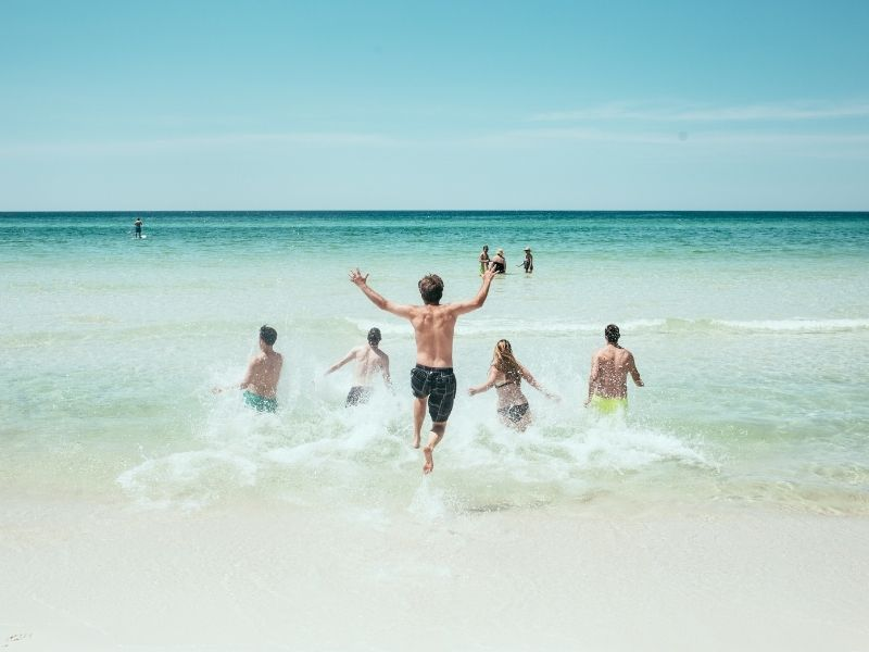 group of beach goers running into the ocean